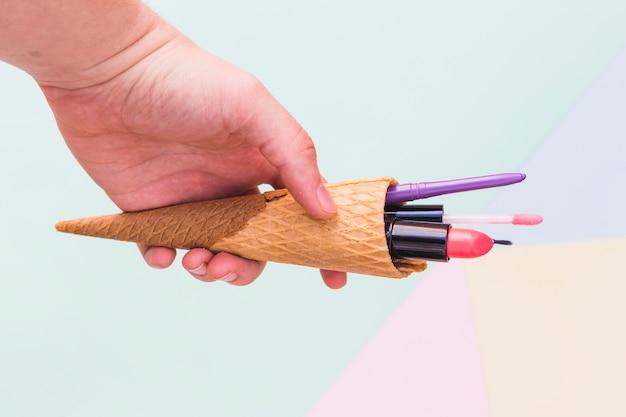 Mão segurando produtos cosméticos na casquinha de sorvete no fundo colorido