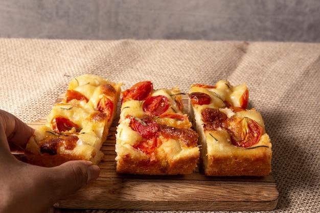 Mão segurando pugliese focaccia com alecrim, azeite e tomate sobre a mesa de madeira.