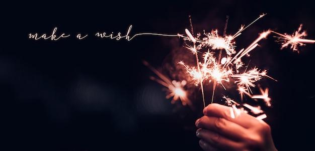 Mão, segurando, queimadura, sparkler, explosão, com, faça, um, desejo, palavra, ligado, um, pretas, bokeh, fundo