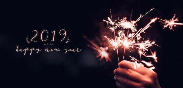 Mão, segurando, queimadura, sparkler, explosão, com, feliz ano novo, 2019, ligado, um, pretas, bokeh, fundo