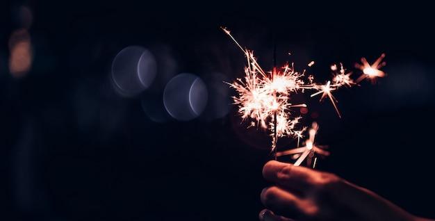 Mão, segurando, queimadura, sparkler, explosão, ligado, um, pretas, bokeh, fundo, à noite