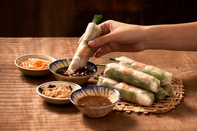 Mão segurando rolinho primavera vietnamita acima da tigela com molho de soja