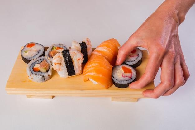 Mão segurando rolos de sushi frescos japoneses tradicionais isolados no fundo branco.