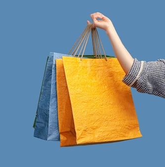 Mão segurando sacolas de papel coloridas