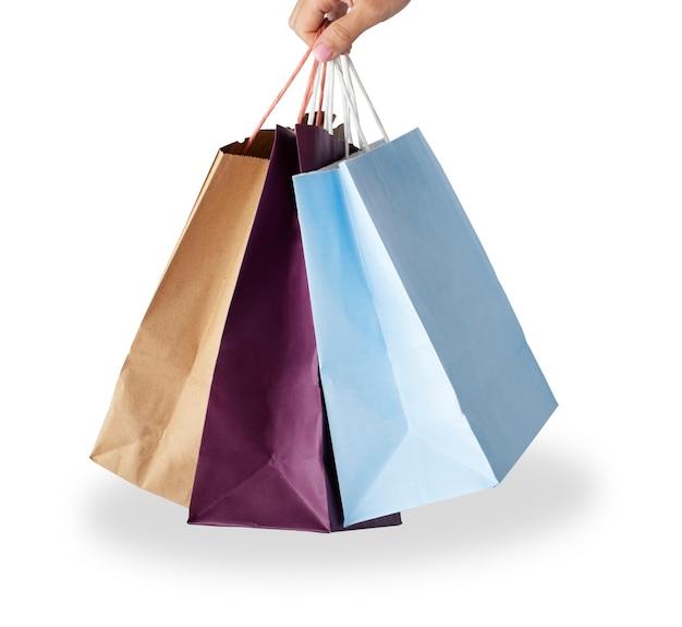 Mão segurando sacolas de papel imagem isolada no fundo branco conceito de venda de compras