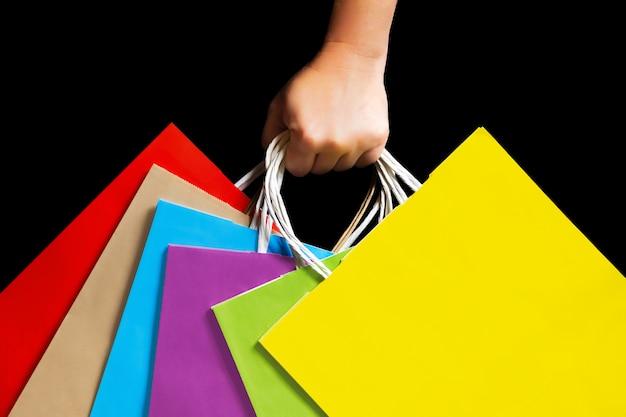Mão segurando sacos de papel colorido.