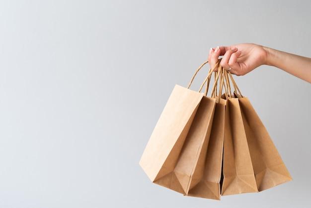 Mão segurando sacos de papel com cópia-espaço