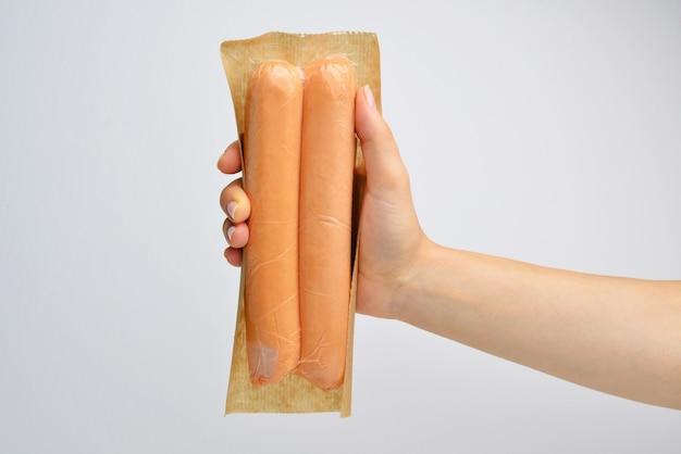Mão segurando salsicha no isolamento de fundo branco