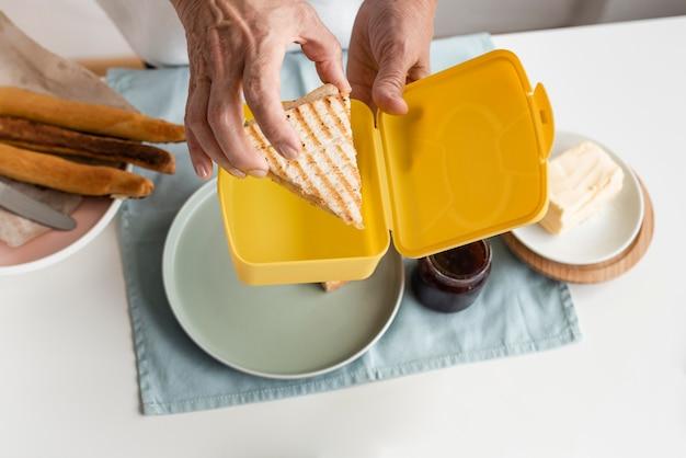 Mão segurando sanduíche de perto