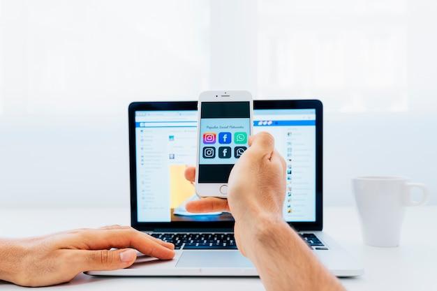 Mão segurando smartphone e laptop em segundo plano