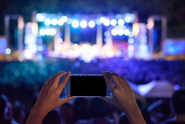 Mão segurando smartphone fotografando concerto ao vivo
