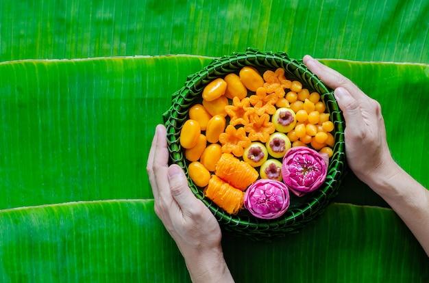 Mão segurando sobremesas de casamento tailandês em um prato de folhas de bananeira ou krathong para cerimônia tradicional tailandesa em folha de bananeira