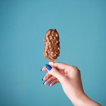 Mão segurando sorvete de chocolate