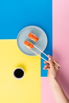 Mão segurando sushi com pauzinhos de perto