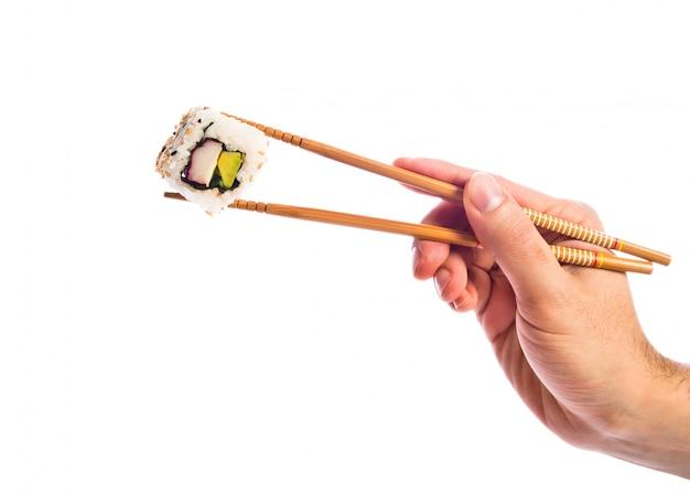 Mão segurando sushi com pauzinhos