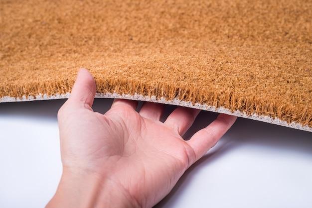 Mão segurando tapete capacho marrom, texturizado, isolado