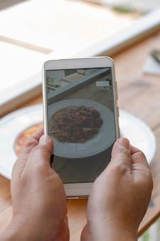 Mão segurando telefone inteligente pegue a foto de comida na cantina