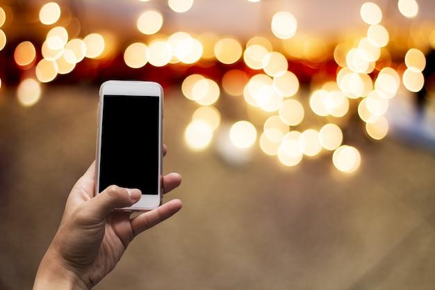 Mão, segurando, telefone móvel, vazio, tela, obscurecido, bokeh, fundo