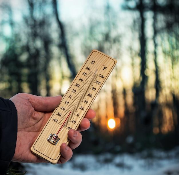 Mão segurando termômetro com temperaturas abaixo de zero