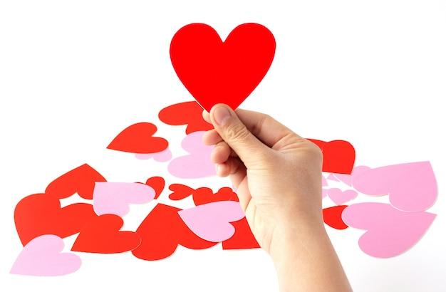 Mão segurando um artesanato de papel em forma de coração vermelho isolado, artesanato de papel em forma de coração vermelho e rosa estão espalhados, conceito de amor e dia dos namorados.