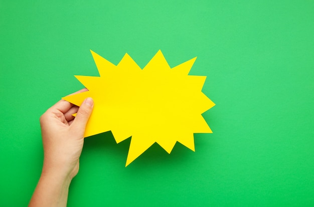 Mão segurando um balão amarelo vazio em verde