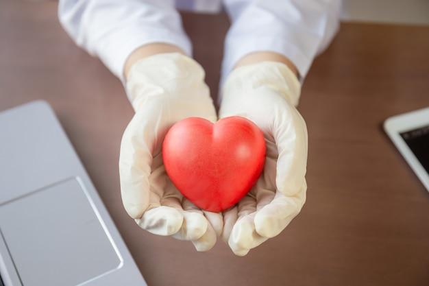 Mão segurando um balão de coração vermelho, mulher médica com cervo vermelho na mão