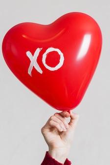 Mão segurando um balão de coração