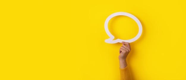 Mão segurando um balão de diálogo sobre fundo amarelo, layout panorâmico