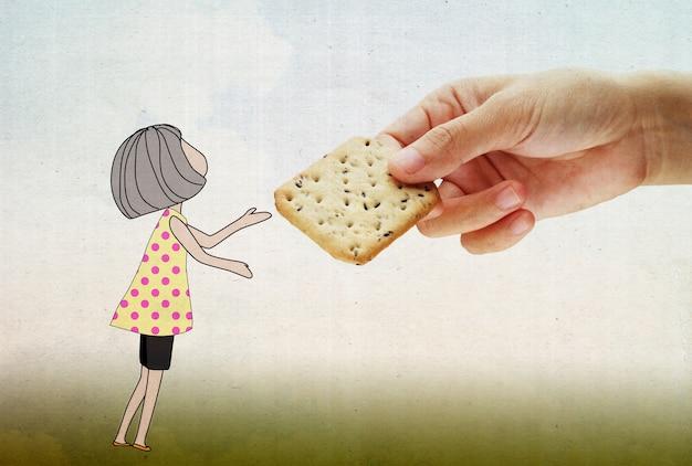 Mão segurando um biscoito com garota minúscula fofa