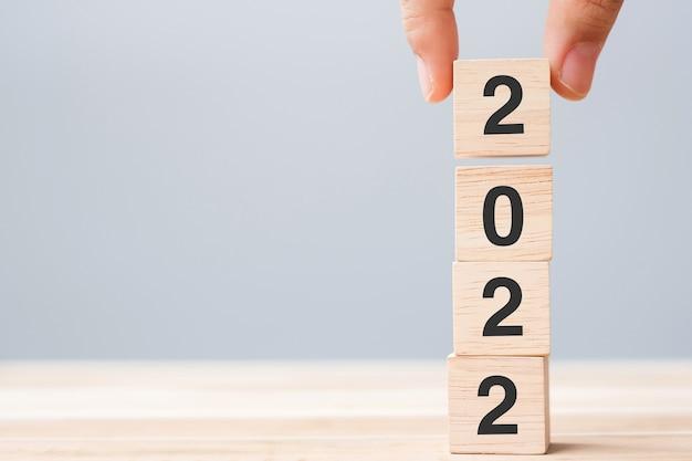 Mão segurando um bloco de cubos de madeira com texto de 2022 no fundo da mesa. conceitos de resolução, plano, revisão, meta, início e feriado de ano novo
