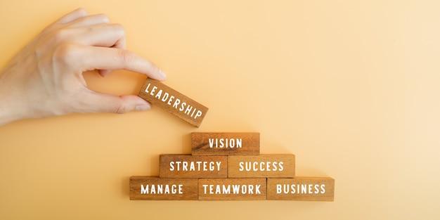 Mão segurando um bloco de madeira e coloque no topo a palavra liderança