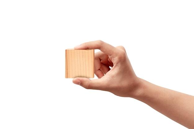 Mão segurando um brinquedo de bloco de madeira isolado sobre o branco