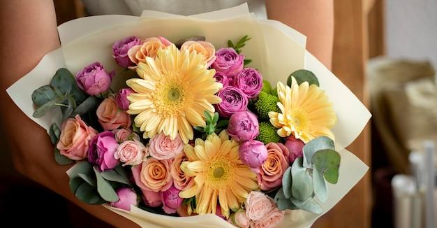 Mão segurando um buquê de flores de perto