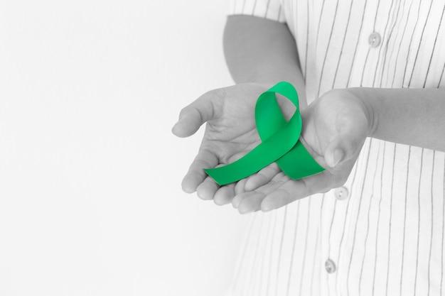 Mão segurando um cacho de fita verde esmeralda ou verde jade em um fundo branco com espaço de cópia