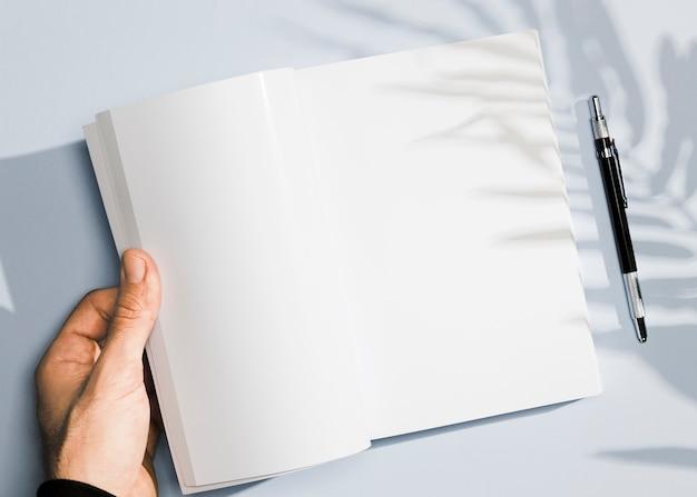Mão segurando um caderno vazio e caneta