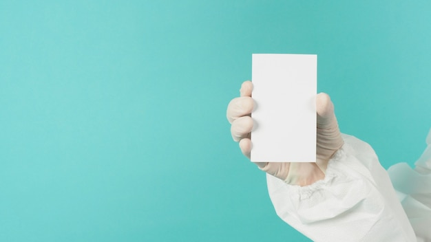 Mão segurando um cartão branco em branco vazio. mão com terno ppe, luva de látex em fundo verde ou azul tiffany espaço vazio para texto