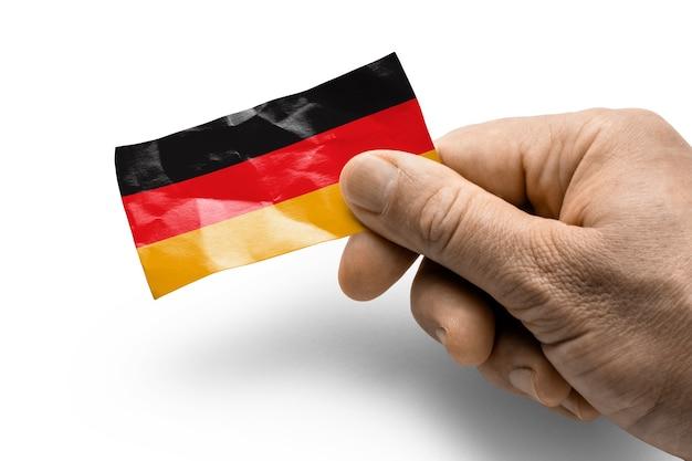 Mão segurando um cartão com uma bandeira nacional da alemanha.