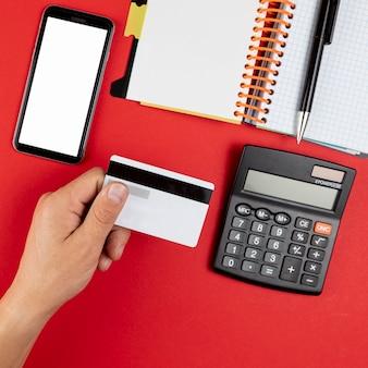 Mão segurando um cartão de crédito ao lado de um telefone simulado