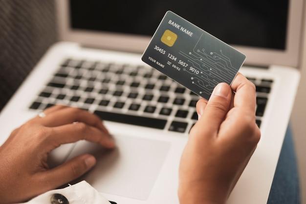 Mão segurando um cartão de crédito e trabalhando no laptop