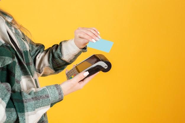 Mão segurando um cartão de crédito e um dataphone