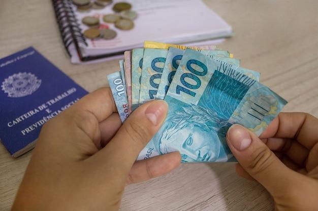 Mão segurando um cartão de dinheiro brasileiro no fundo