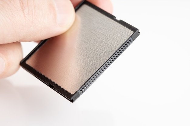 Mão segurando um cartão de memória compactflash na superfície branca. equipamento fotográfico. copie o espaço