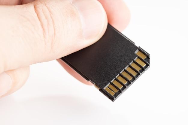 Mão segurando um cartão de memória sd na superfície branca. equipamento fotográfico. copie o espaço