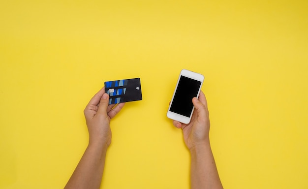 Mão segurando um cartão de pagamento com funções wi-fi e um telefone em uma parede amarela