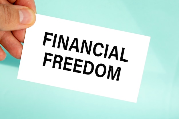 Mão segurando um cartão de visita de papel com liberdade financeira de texto, plano de fundo cinza claro closeup, conceito de negócio