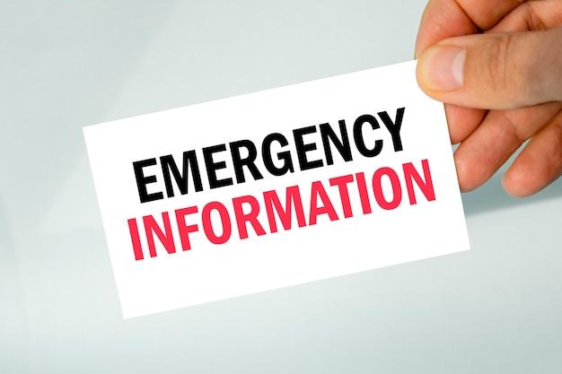 Mão segurando um cartão de visita de papel com o texto informações de emergência, plano de fundo cinza claro closeup, conceito de negócio