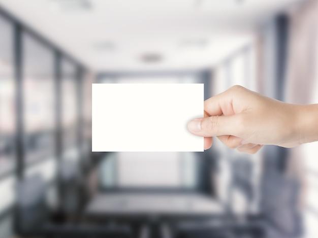 Mão segurando um cartão de visita em branco com fundo de escritório