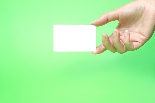 Mão segurando um cartão de visita em branco. o conceito de transferência digital de dinheiro, banco e e-commerce.