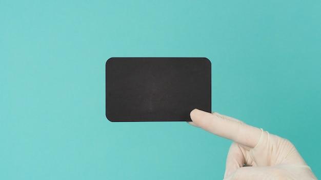 Mão segurando um cartão preto em branco vazio. mão com terno ppe, lmão segurando um cartão preto em branco vazio. mão com terno preto, luva de látex em verde menta ou fundo azul tiffany. espaço vazio para texto