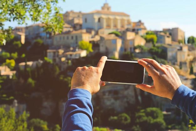 Mão segurando um celular tirando foto da vila de gordes